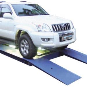 Le véhicule à inspecter se positionne sur une rampe basse et un système de caméra vérifie le châssis